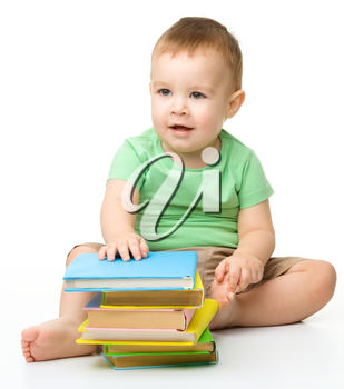 Portrait of a cute little boy with books, isolated over white