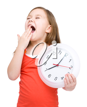 Little girl is holding big clock while yawning, isolated over white