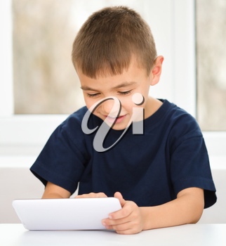 Young boy is using tablet while sitting at table, isolated over white