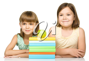 Cheerful little girls with books and green apple are sitting at table, isolated over white