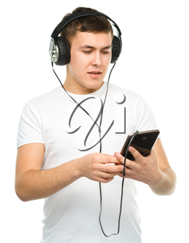 Closeup portrait of young man enjoying music using headphones, isolated over white