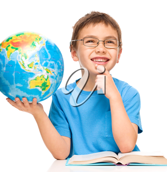 Little boy is holding globe while daydreaming, isolated over white