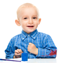 Portrait of a cute little boy playing with paints, isolated over white