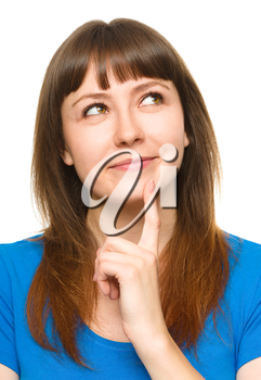 Portrait of a happy young woman thinking about something while touching her chin with finger, isolated over white