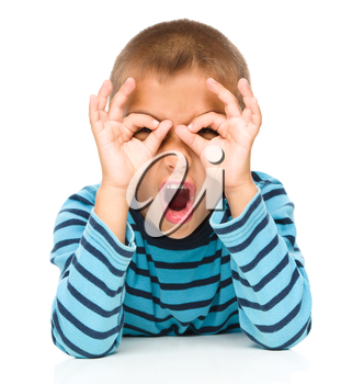 Astonished little boy is showing glasses gesture, isolated over white