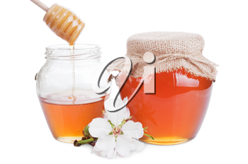 glass jars with honey and wooden stick isolated on white background