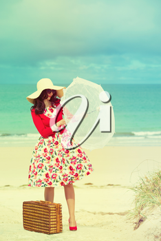 beautiful lady in red with umbrella near the sea in retro style