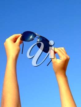 Royalty Free Photo of Female Hands Holding Sunglasses Up to the Sky