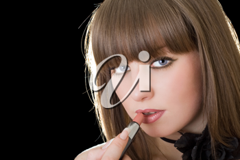 Royalty Free Photo of a Woman Putting on Lipstick