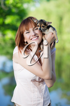 Young smiling red-haired woman posing with a funny little dog