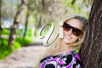 Portrait of pretty blond woman wearing sunglasses and posing near the tree