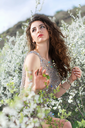 Beautiful curly caucasian lady wearing grey dress posing in blooming garden