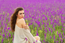 Sexy curly brunette showing her bare shoulder in a flowering field