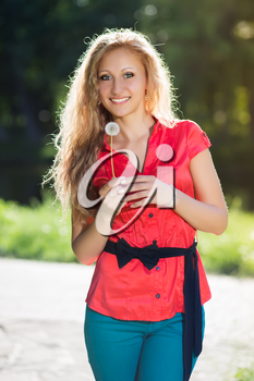 Pretty young blond woman posing with a dandelion