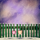 snow-covered wooden fence with two paper hearts