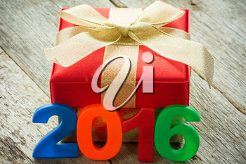 Gift box with golden ribbon and a 2016 sign on wooden background
