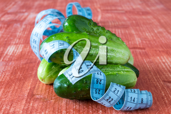 Cucumber fruits and tailor measuring tape on grey wooden background