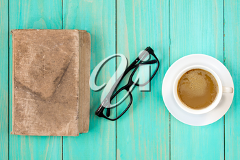 Old book with glasses and coffee cup on wooden background