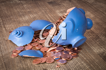 Broken piggy bank with coins scattered on the table