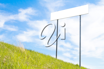 Blank sign board on a background of green grass and blue sky