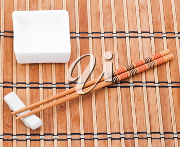 Chopsticks and bowl on bamboo background