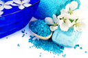 The blue salt in a wooden spoon, soap, towel, a bowl of water and white flowers of apple isolated on white background