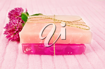 Two homemade pink soap, tied with hemp rope, two flowers pink clover on the terry towel