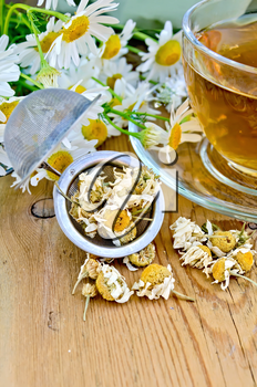 Herbal tea in a glass cup, metal sieve with dry chamomile flowers, fresh flowers, daisies, doily on a wooden board