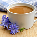 Chicory drink in a white cup with flower and napkin on a wooden boards background