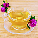 Herbal tea with flowers of clover in a glass cup on a bamboo napkin