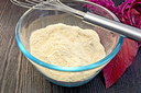 Amaranth flour in a glass bowl with mixer, purple amaranth flower on the background of wooden boards