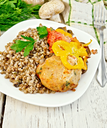 Cutlet of turkey meat with buckwheat, mushrooms, tomatoes and peppers in the dish, parsley, a towel and a fork on the background of wooden boards