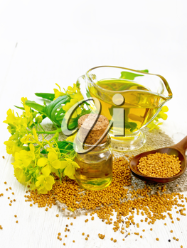 Mustard oil in a glass bottle and gravy boat, grains in a spoon and burlap, yellow mustard flowers on wooden board background
