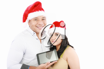 Two smiling couple holding tablet touch pad with hat santa