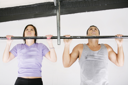 Young adult fitness woman and man preparing to do pull ups in pull up bar.
