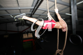 Crossfit rope climb training on a dark background.