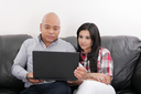 Young couple thinking and looking at a laptop computer