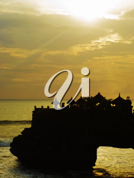 Tanah lot small temple on the rock silhouette at sunset, Bali, Indonesia