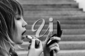Closeup image of beautiful young woman with lipstick and mirror in her hands. Black and white photo
