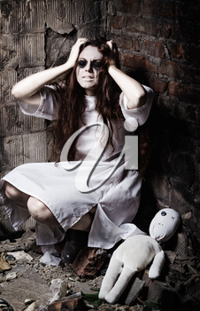 Horror style shot: the strange crazy girl and her moppet doll