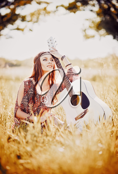 Portrait of a lovely young hippie girl with guitar. Outdoor shot