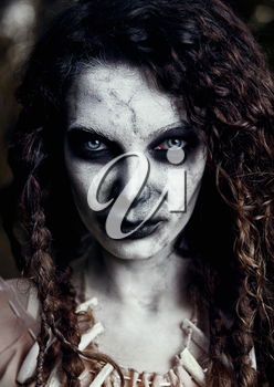 Halloween theme: creepy grim voodoo witch. Close-up portrait of the evil sorceress. Zombie woman (undead)