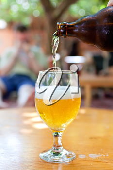 Royalty Free Photo of a Bottle of Beer Being Poured at a Bar