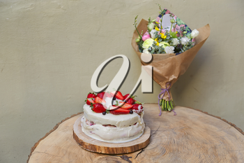 Strawberry cake on wooden table with flowers bouquet