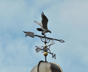 a weather vane on a roof against a sky