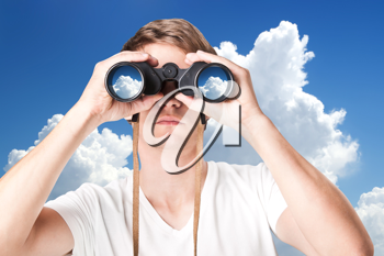 Closeup of handsome young man looking through binoculars against sky