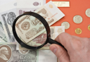 Royalty Free Photo of a Person Using a Magnifying Glass to Look at Money