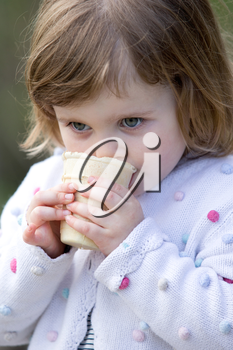 little girl eating an ice cream outdoors