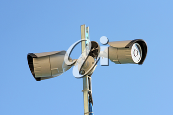 Two security cameras against blue sky
