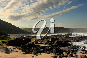 Picture of White Clouds and Blue Skies with Black Rocks and Beach